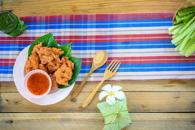 Camarão frito empanado com acompanhamentos em fundo de madeira