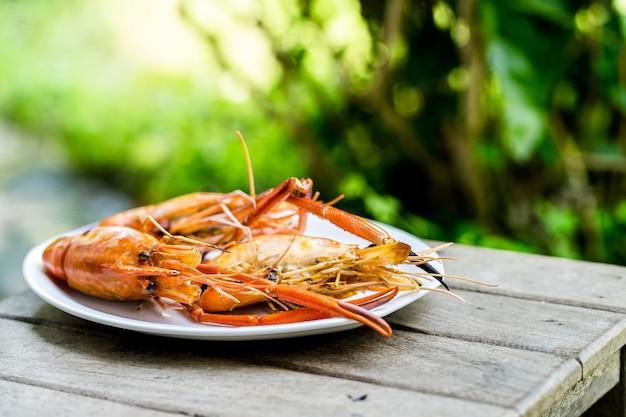 Camarão grelhado, coloque camarões no prato branco, close-up frutos do mar grelhados, coloque na mesa de madeira