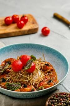 Camarão grelhado com molho de tomate e arroz fecha no prato na mesa de concreto com ingredientes no fundo