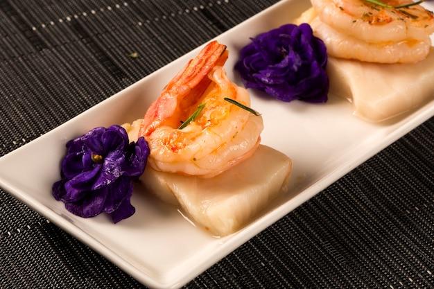 Camarão grelhado com unha de peixe cru em prato branco à mesa