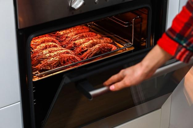 Camarão grelhado e camarão frito no forno da cozinha de casa e mão segurando a porta
