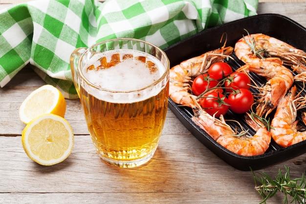 Camarão grelhado na frigideira e cerveja na mesa de madeira