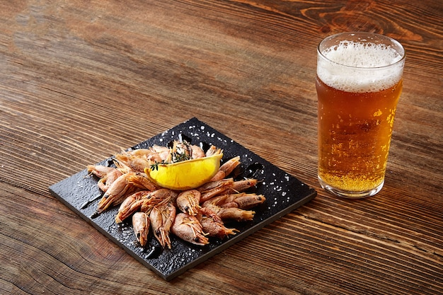 Camarão grelhado na frigideira preta e cerveja na mesa de madeira