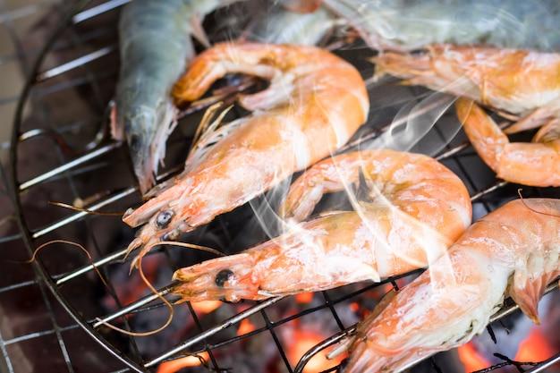 Camarão grelhado no fogão em chamas no acampamento de festa