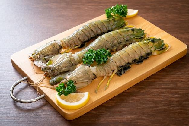 Camarão mantis fresco com limão na tábua de madeira