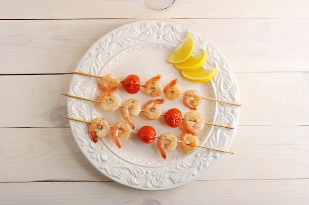 Camarão no espeto com tomate cereja no espeto de madeira e fatias de limão