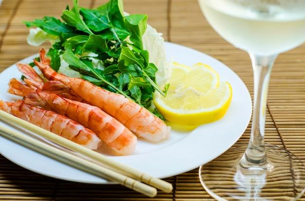 Camarão no prato com limão e salada