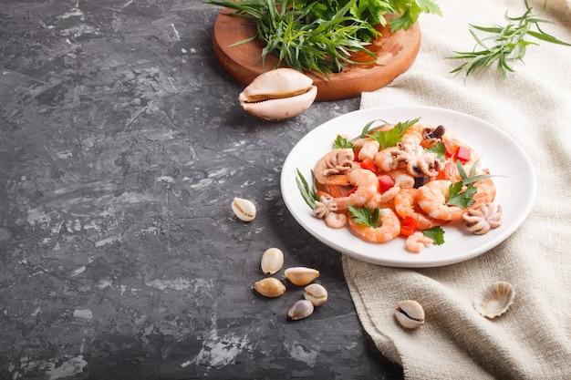 Camarão ou camarão cozido e polvos pequenos na placa cerâmica branca sobre um fundo preto de concreto e têxteis de linho. vista lateral, copie o espaço.