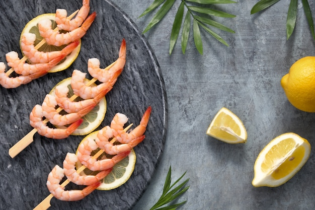 Camarão picante de limão e alho em palitos de madeira, deitado na pedra escura