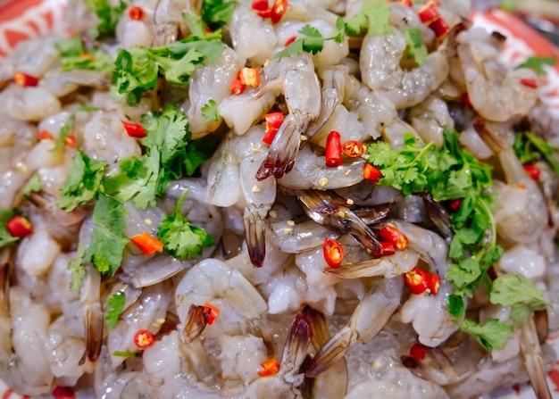 Camarão picante e ácido cru para a venda em um mercado de produto fresco local em tailândia.