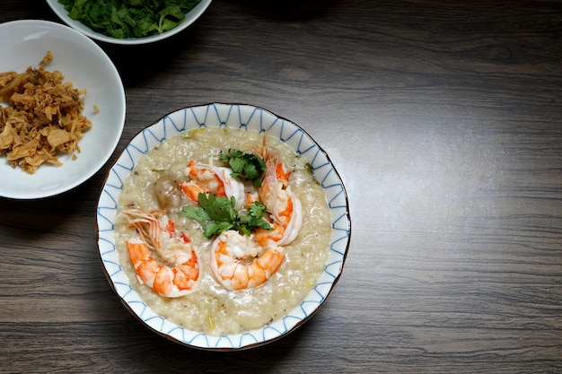 Camarão sopa de arroz cozido com mingau de camarão em uma tigela e picles de nabo e coentro na mesa de madeira