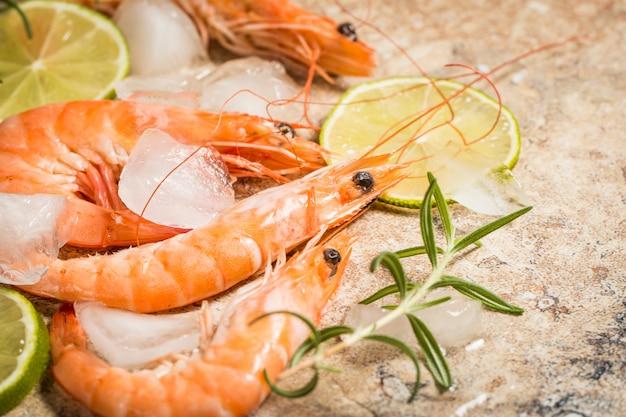Camarão tigre com limão, limão, alecrim e pimenta preta em pedra. camarões saborosos frescos prontos para serem cozinhados.