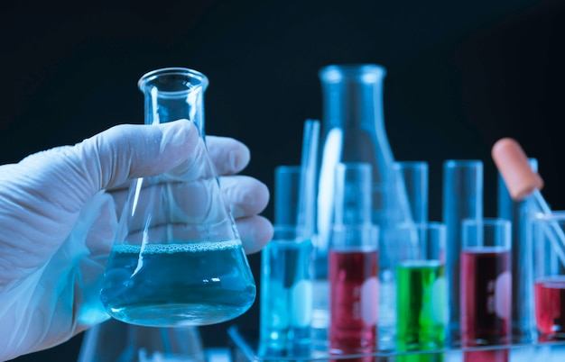 Câmaras de ar químicas do laboratório de vidro com líquido para o conceito analítico, médico, farmacêutico e da pesquisa científica.