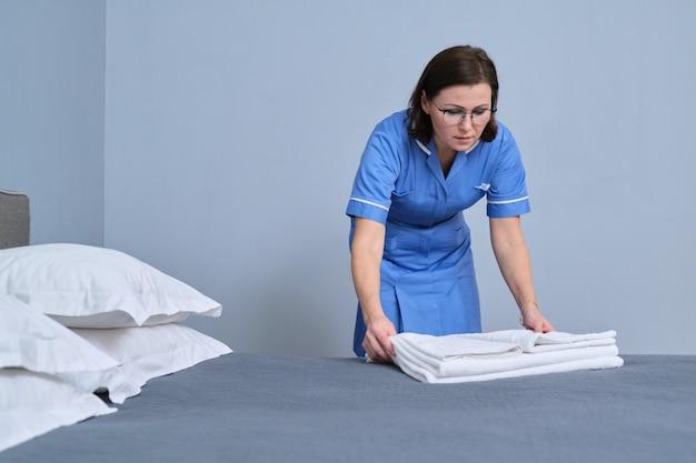 Camareira fazendo a cama de hóspedes no quarto do hotel, colocando lençóis limpos. serviço, limpeza, equipe, conceito de hotel