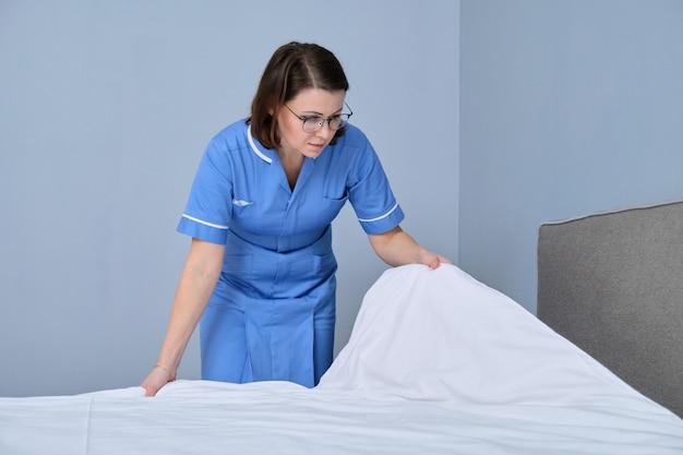 Camareira fazendo cama de hóspede em quarto de hotel