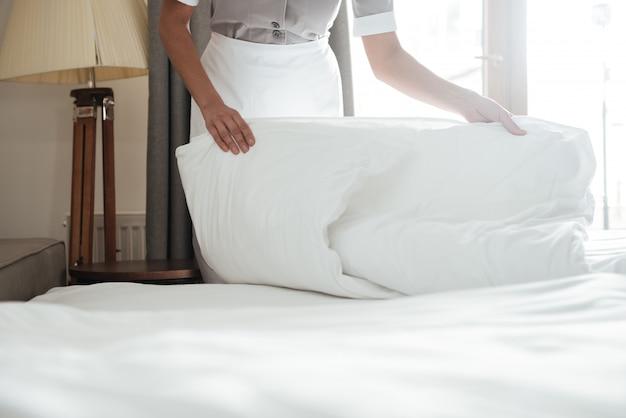 Camareira fazendo cama no quarto de hotel