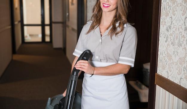 Camareira feminina do hotel com aspirador de pó