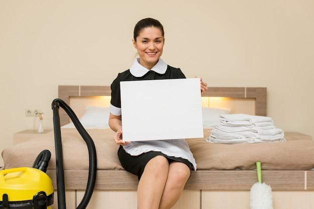 Camareira no quarto de hotel com laptop