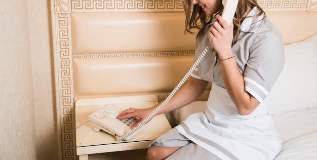 Camareira sentado na cama fazendo chamada no telefone do hotel