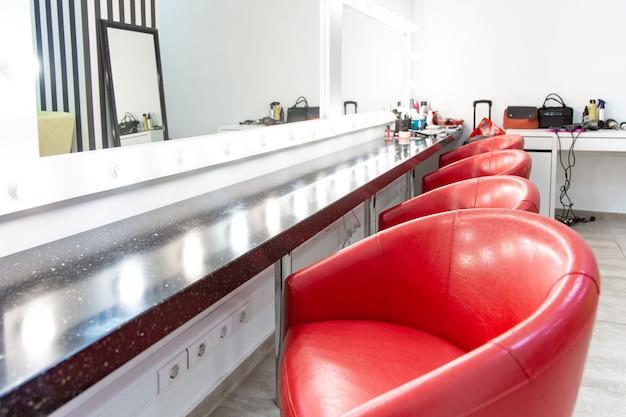 Camarim luminoso com cadeiras vermelhas. uma sala simples para maquiagem, várias cadeiras confortáveis estão enfileiradas.