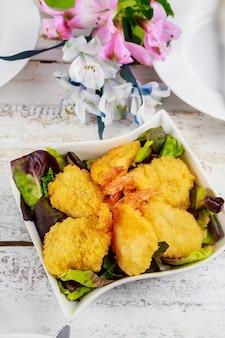 Camarões à milanesa fritos com salada e mesa posta.