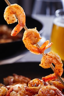 Camarões amarrados em um espeto. camarão frito em uma panela com alho e limão em um prato preto e um copo de cerveja