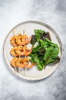 Camarões assados, camarões no espeto com salada de espinafre