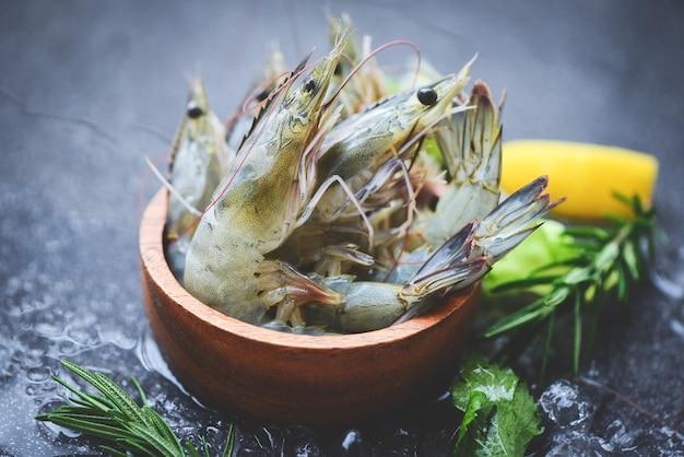 Camarões crus camarões no gelo em uma tigela, camarão fresco, frutos do mar com ervas e especiarias