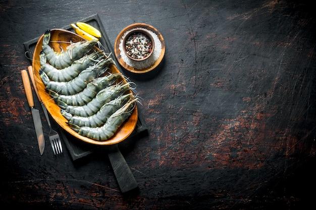 Camarões crus em uma placa de corte com especiarias e fatias de limão. em rústico escuro