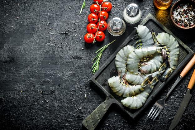 Camarões crus em uma placa de corte com tomate cereja e especiarias. em preto rústico