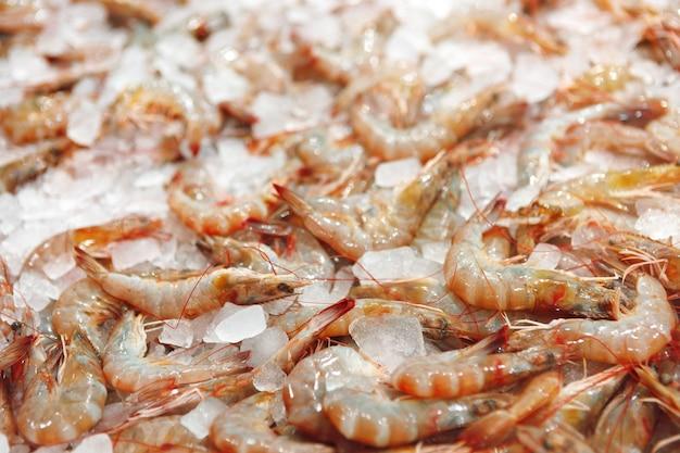 Camarões crus frescos fecham deitado no gelo no supermercado