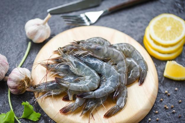 Camarões crus na tábua de madeira chapeiam camarões frescos de camarão para cozinhar