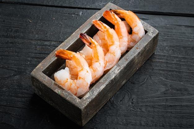 Camarões de camarão rei crus, frescos, descascados e com cauda definida, em caixa de madeira, sobre mesa de madeira preta