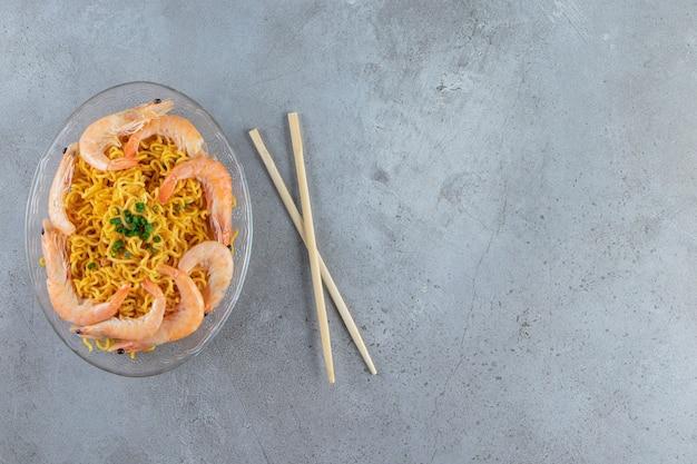 Camarões e macarrão em um prato de vidro ao lado de pauzinhos, no fundo de mármore.
