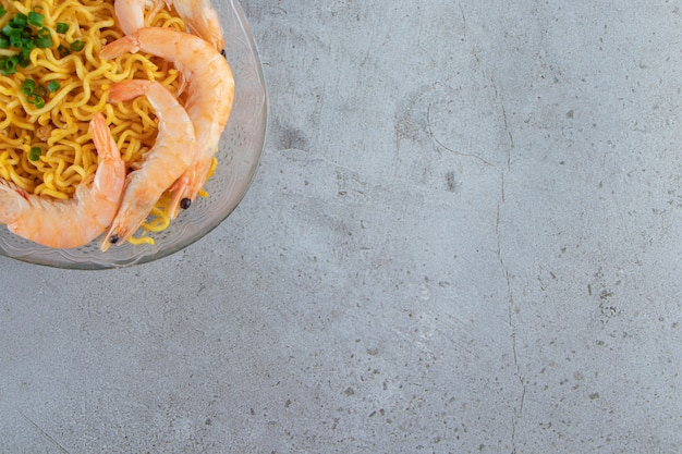 Camarões e macarrão em um prato de vidro, no fundo de mármore.