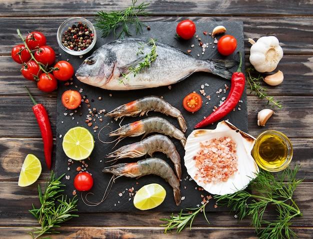 Camarões frescos crus e peixe dourado