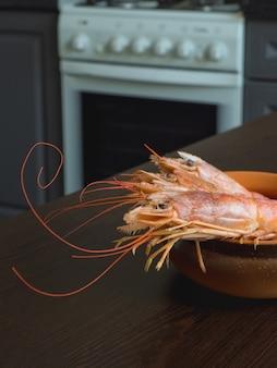 Camarões frescos na mesa da cozinha em uma tigela.