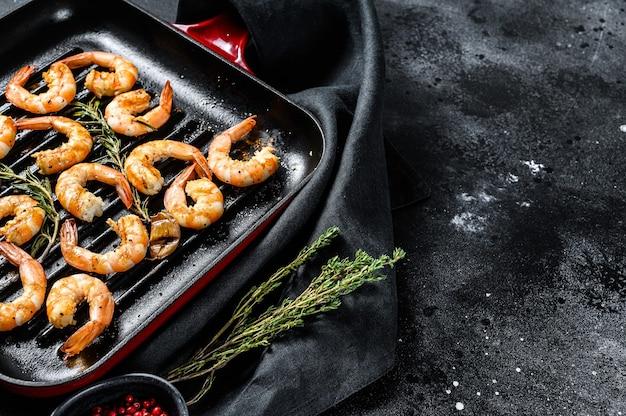 Camarões fritos, camarões em uma panela. fundo preto