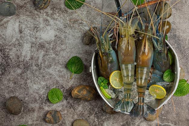 Camarões grandes e frescos, prontos para cozinhar decorados com belos acompanhamentos.