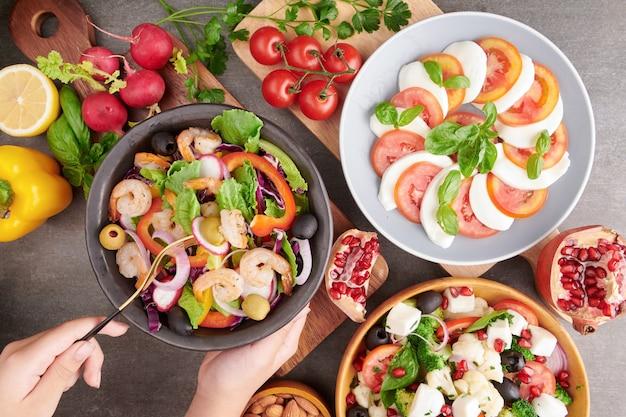 Camarões grelhados e salada de legumes fresca. comida saudável. postura plana. salada caprese italiana com tomate, manjericão, mussarela, ingredientes da salada caprese tradicional italiana. salada grega mediterrânea.