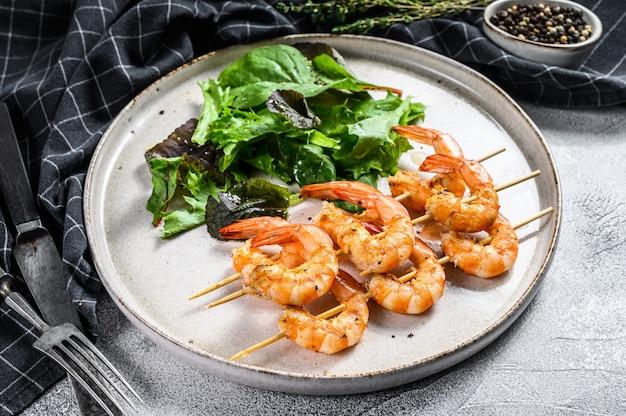 Camarões grelhados, espetos de camarão com ervas, alho, espetada de brochette. .