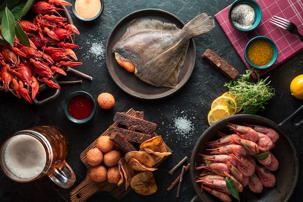 Camarões grelhados, lagostas, peixes chatos em uma placa e caneca de cerveja. fundo da mesa de madeira escura.