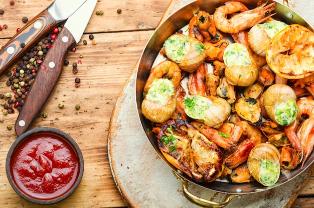 Camarões grelhados, mexilhões e caracóis recheados. deliciosos frutos do mar na mesa de madeira