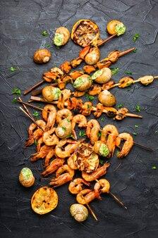 Camarões grelhados, mexilhões e caracóis recheados. deliciosos frutos do mar no espeto
