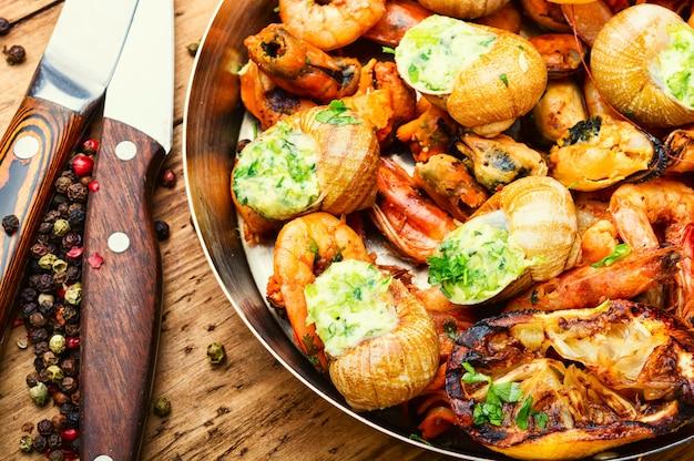 Camarões grelhados, mexilhões e caracóis recheados na frigideira