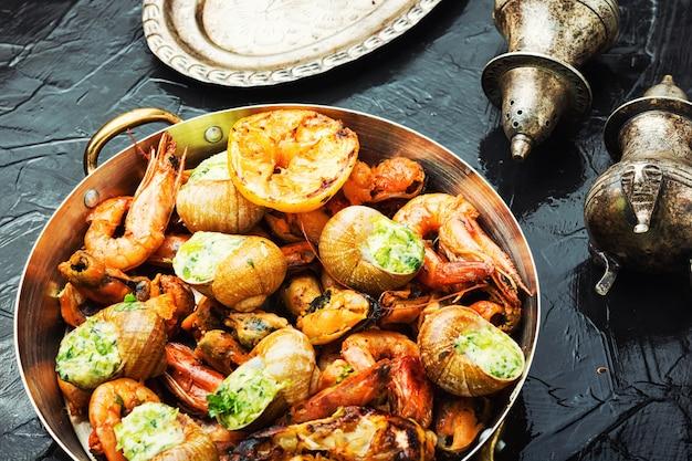 Camarões grelhados, mexilhões saborosos e caracóis recheados. frutos do mar deliciosos.