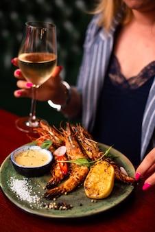 Camarões lagostins deliciosos no restaurante em uma mesa de madeira, sem pessoas visíveis. saborosos frutos do mar com vinho no café.