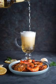 Camarões ou camarões grelhados são servidos com alho e limão e molho de frutos do mar e cerveja leve e espumosa