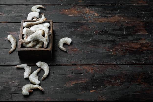 Camarões tigre crus congelados e crus, conjunto de camarões, na velha mesa de madeira escura, com espaço de cópia para o texto