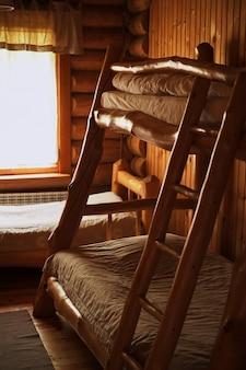 Camas de madeira de beliche em um quarto de madeira de albergue dim iluminação